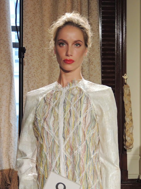 Model wears white panelled dress with woven details