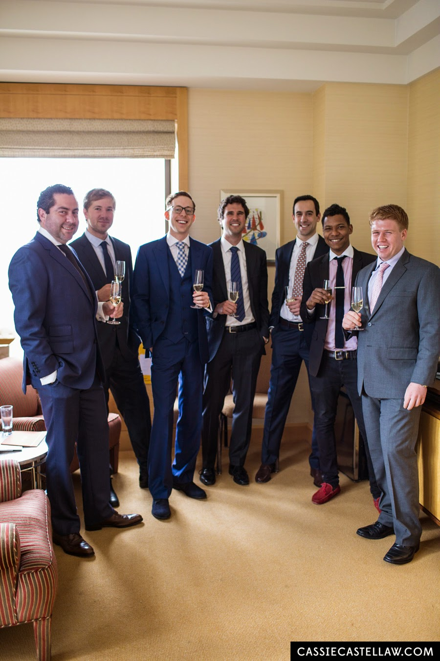 Groom and groomsmen smiling, toasting with champagne in suite at Four Seasons Hotel New York. NYC Lifestyle wedding photography by Cassie Castellaw. www.cassiecastellaw.com