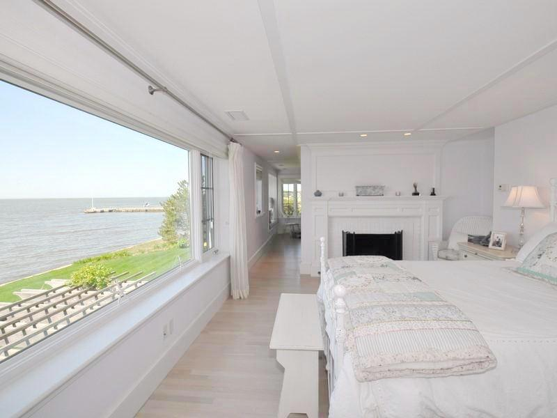 White master bedroomwith a light wood floor, bench style ottoman at the foot of the bed, a fireplace and a picture window with a view of the Long Island Song