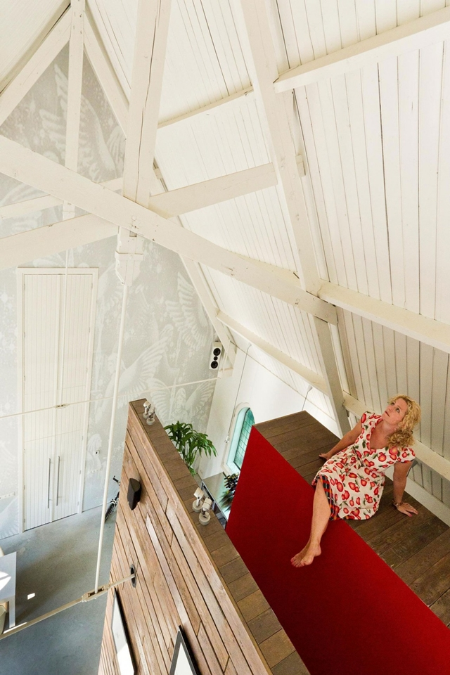 Picture of woman sitting on the wooden structure with red staircase to the mezzanine floor