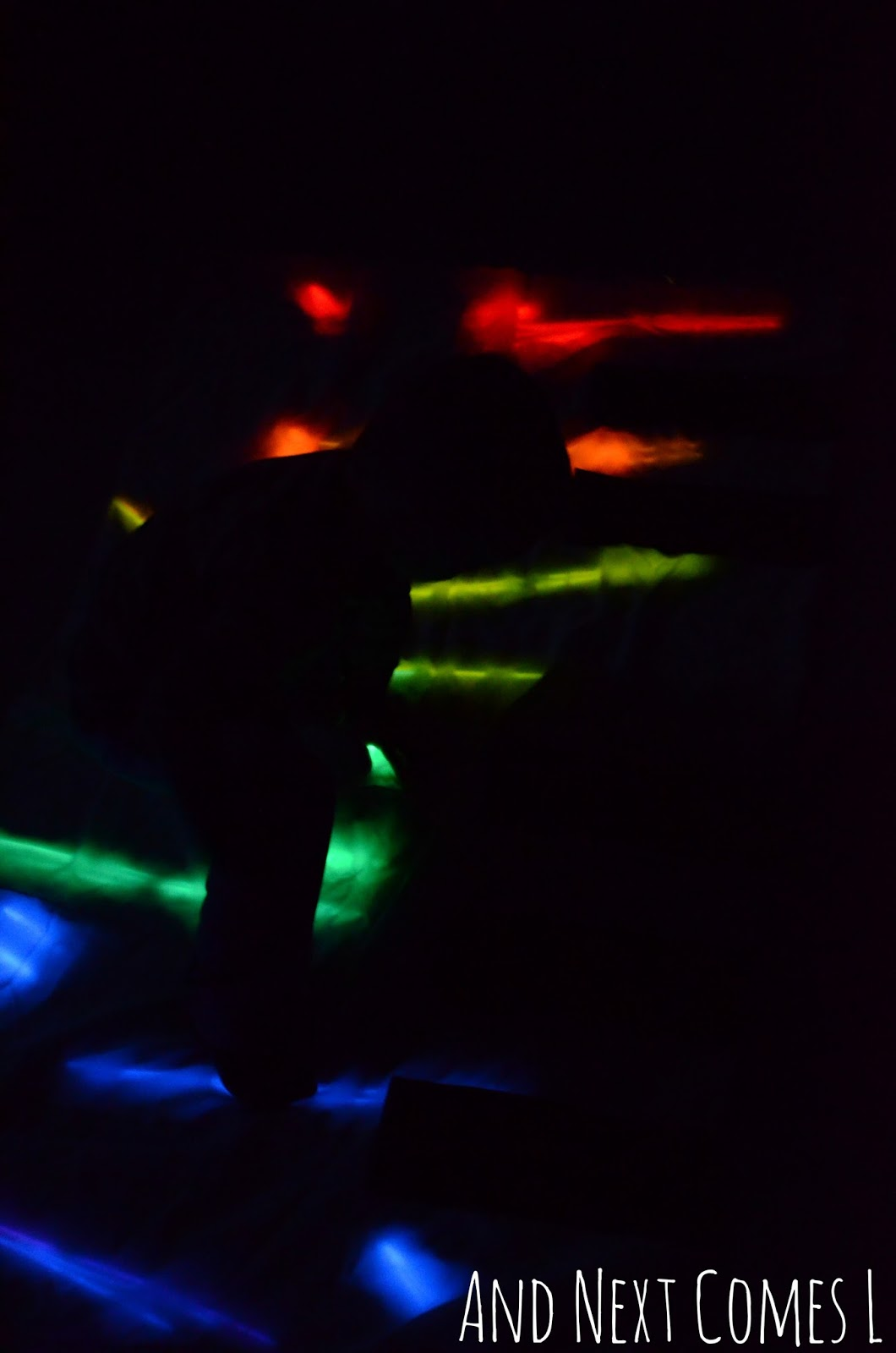 Silhouette against a homemade glowing floor piano from And Next Comes L