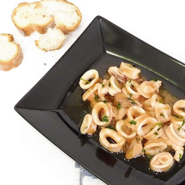 Plato de calamares con trozos de pan sobre fondo blanco