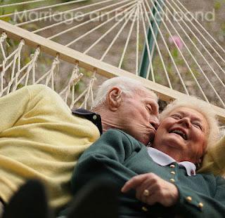 An elderly couple kissing