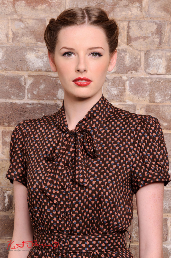 Strong and feminine branding shot of model in chocolate brown patterned 40's style blouse, mid shot - photographed against a distressed brick wall in the studio - studio fashion photography