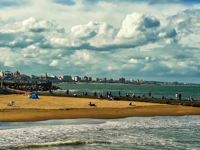 Pescadores en la escollera, gente en larena,el mar,y la ciudad de Mar del Plata bajo un manto de nubes