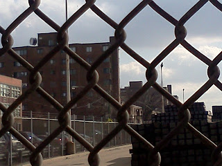 View of a Chicago Housing Development thru a chain linked fence symbolizing oppression