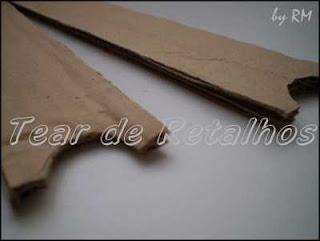 Recortando uma meia lua nas extremidades da régua de papelão para fazer uma navete