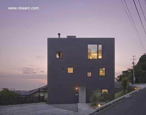 Fachada principal con acceso vista nocturna de la casa cúbica de concreto en Japón