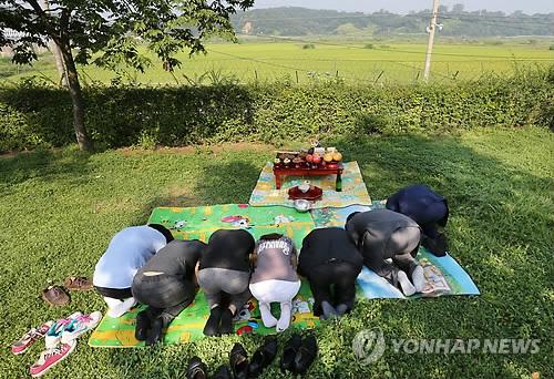 Surcoreanos haciendo una reverencia hacia Corea del Norte