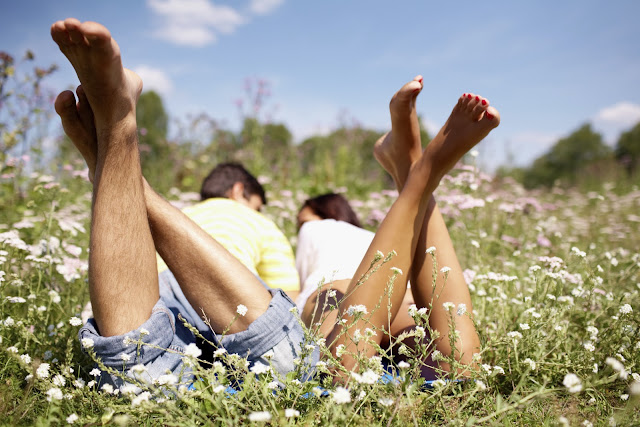 Affectionate couple enjoying a sunny day laying in the grass.