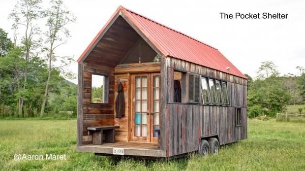 Casa pequeña de madera sobre ruedas con porche en un extremo