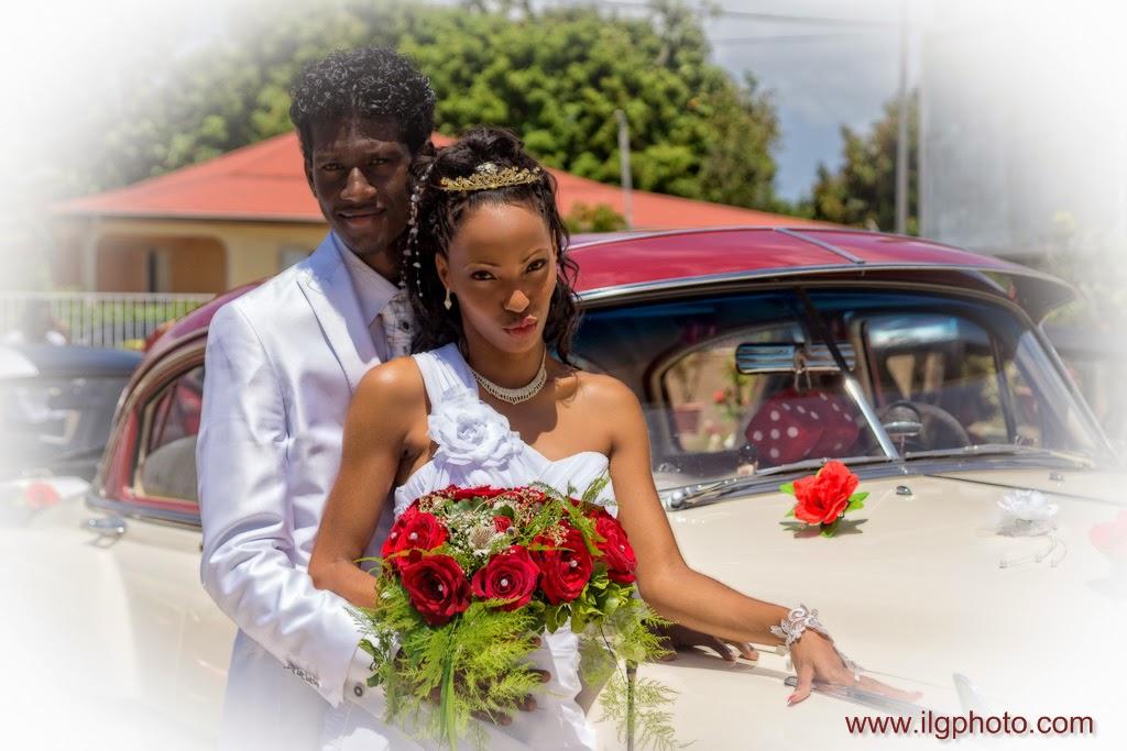 mariés posant devant vieille voiture