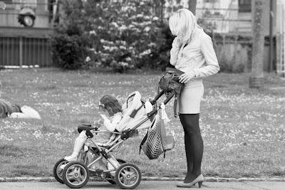 Ist dies eine moderne Geschäftsfrau, schick mit Kinderwagen und Mobiltelefon unterwegs?