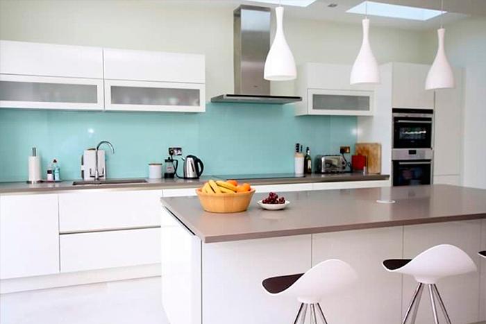 Cozinha moderna com eletrodomésticos em inox e detalhes em verde água