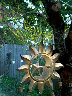 Sun Sculpture hanging from tree with Blossoms in Background