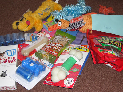 Picture of all the toys and such The Hound Dog's sent us... including stuffies, dog treats, clean up bags, and nylabones