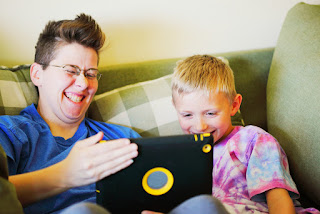 child and woman laughing with tablet