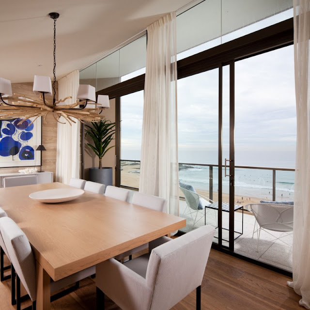 Photo of modern dining table by the balcony window with the view of the beach