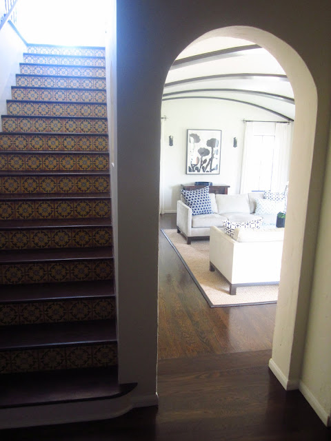 foyer with staircase with Spanish tiles and view into living room