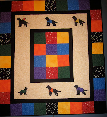 This is a picture of the completed dog guide quilt that is being raffled off. There are six main brightly coloured fabrics in the quilt. A rosy red patterned with small white bones and brown paw prints. An ocean blue covered in tiny, lighter blue paw prints. A sunshine yellow covered in straight rows small, darker yellow dots. A dark green with a leafy pattern. A vibrant orange with a swirly pattern. And finally, a deep purple covered in lighter purple 5-point stars of different sizes. The centre of the quilt is a 3 by 4 rectangle of squares, 2 each of the 6 colours. Around the centre is a thin border of a plain black fabric. Around that is a thick (8 inch or so) border of a beige fabric. This fabric matches the red fabric, with a pattern of white bones and light brown paw prints. Within this beige fabric are six black lab silhouettes - three along the top and three along the bottom. Each represents one of the dog guide programs and has a jacket cut out of one of the six main colours of the quilt. In the top left corner, a canine vision dog wearing a brown harness with a small red harness sign with a single paw print on it. Next is a special skills dog in a blue saddle-bag type harness. In the top right, a seizure response dog in a small yellow jacket covering the rib area. In the bottom left is a foster puppy in a green jacket covering most of its back - this silhouette is smaller than the others, and facing the right whereas the other five are facing left. In the bottom centre in the hearing ear dog, with an orange jacket in the same pattern as the yellow seizure one. Finally, in the bottom right, is the autism assistance dog with the larger purple jacket that covers most of its back. All of the dogs are cut out of a softer, suede-like fabric, and have been appliqued onto the quilt. Around the beige fabric is another thin border of plain black fabric. Finally, there is a border of coloured squares. The four corner squares are plain black, and then along each edge there is one of each of the six coloured squares, and one or two of another black fabric covered in small white pawprints. Around the outside edge of the quilt is a very thin black edging, and the back of the quilt is plain black. The fabric is quilted with invisible thread in diagonal lines going both directions across the quilt.