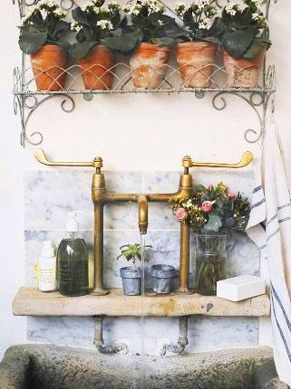 Farmhouse sink with Carrara marble backsplash and a small shelf to holding potted plants and a bouquet of flowers in a vase