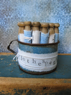 Old Clothespegs wrapped in feedsacks fill a graniteware cup