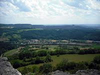 Bild: Blick vom Berg (Staffelberg) ins Tal. Man sieht noch den Felsvorsprung, von dem aus das Bild aufgenommen wurde. Das Tal zeigt eine Wiese, viele Baumreihen, ein kleines Dorf, Äcker und auch Wälder. In der Ferne kann man noch andere Berge erblicken. Der Himmel ist leicht bewölkt.