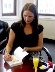 Photo of Marissa Meyer, a pale-skinned woman with long brown hair, signing a copy of Cinder