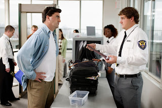 An agry passenger encounters a TSA agent at the security x-ray machine.
