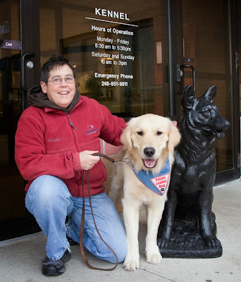 "A woman with short brown hair wearing a red fleece jacket and blue jeans kneels on one knee next to a full-grown golden retriever who is standing and wearing a blue, white and red bandana that says, ""Future Leader Dog.""  The two are next to a black statue of a german shepherd dog. Behind them are glass doors with white letters that tell the hours of the kennel."