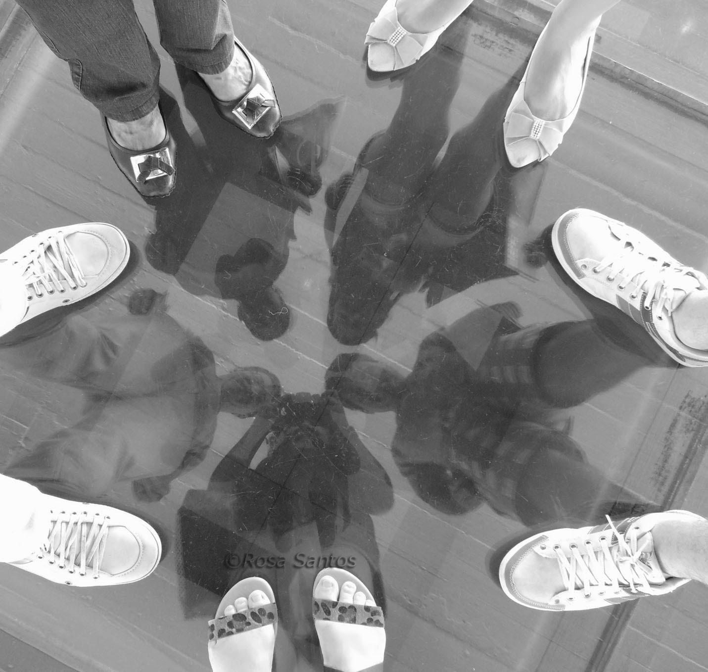 Fotografia monocromática, P e B. Pés calçados de cinco pessoas juntas, estão nítidos, posicionados em círculo sobre piso de vidro transparente. Imagens dos corpos a partir das pernas até as cabeças, apenas são vistos no vidro com baixa nitidez. Os corpos estão concêntricos. No sentido horário, de baixo para cima, uma mulher segurando um objeto, um homem, uma mulher, outra mulher e outro homem.