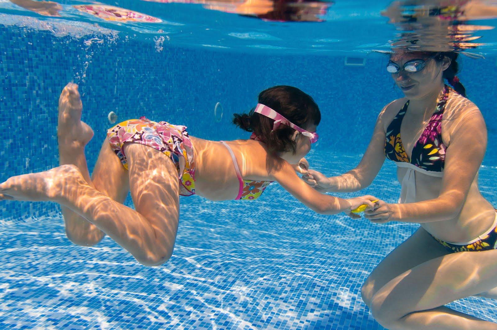 Niña aprendiendo a nadar en la piscina - Underwater photos - Little