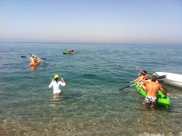 En la imagen se observan tres kayaks con alumnos y monitores remando mar adentro.