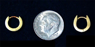 Photo comparing a lost earring with a dime