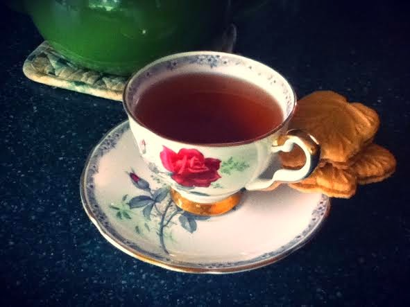 A picture of a cup of earl grey tea and two maple cookies.