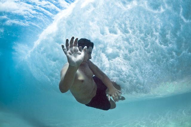 Fotos submersas de banhistas passando debaixo de ondas