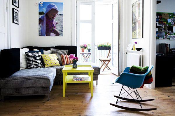 Decoração com sofá de canto, mesa de centro amarela e cadeira de desing Eames