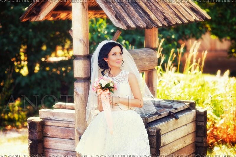 Невеста сидит около колодца с букетом цветов