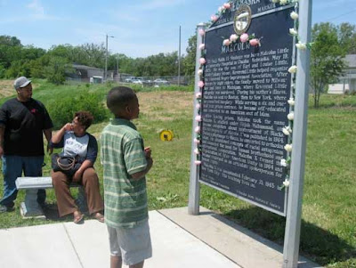 Photo of the Malcolm X birthplace plaque with preteen boy reading it