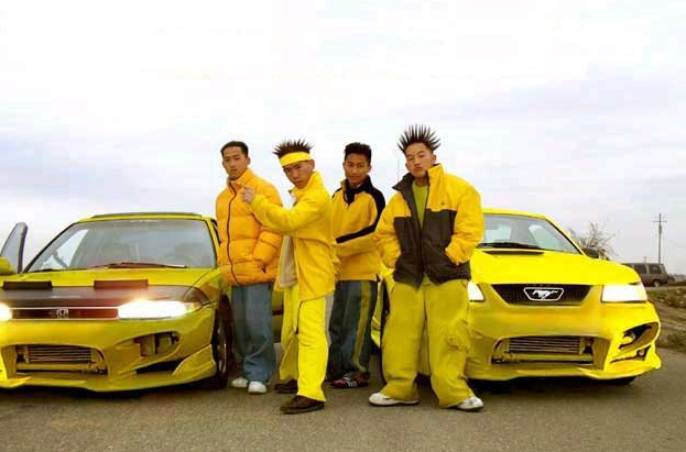 four asian men dressed in yellow, standing in front of yellow sportscars, spiky hair, 2000's
