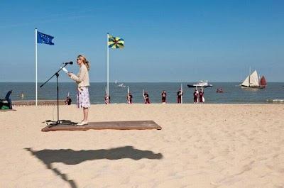 ilusión óptica de mujer en la playa y la bandera