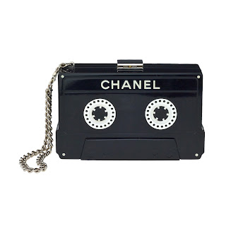 Contemporary black Chanel clutch purse in the shape of a casette tape with silver chain strap.