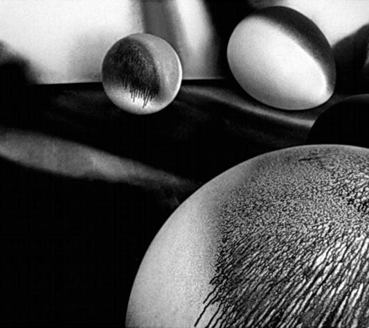 Foto a preto e branco de esferas pintadas com cores fortes, espalhadas no chão.