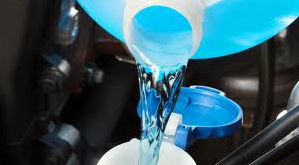 Photo of blue windshield wiper fluid being poured into a vehicle