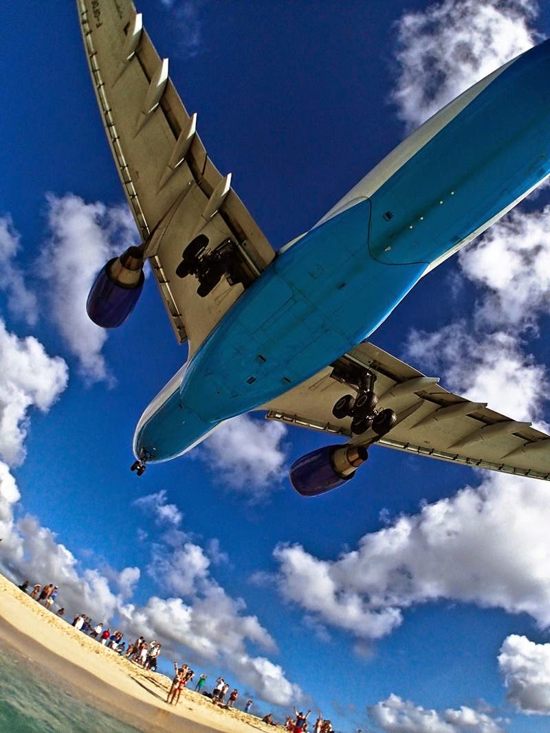 An excited Maho Beach crowd looks up in awe as an Air Caraïbes flight from Paris passed by to land at Princese Juliana Airport, just past the beach.