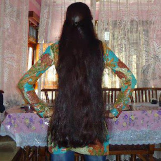 Modern Kerala girl with long hair in her bed room.
