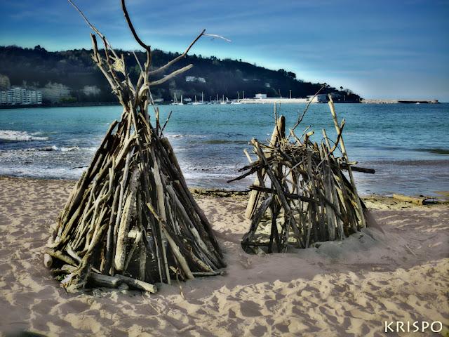 dos chabolas hechas con maderas de deriva en playa de Hondarribia