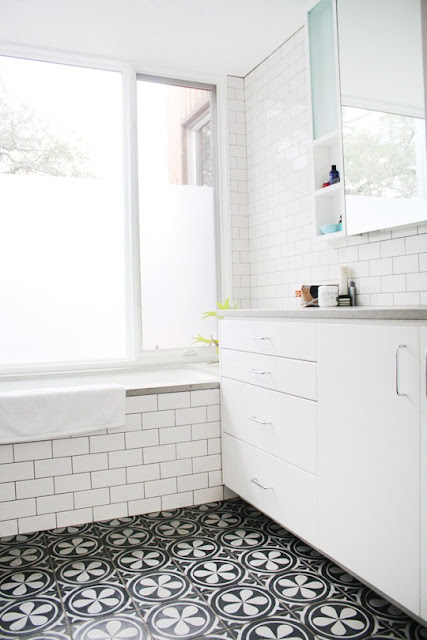 Bathroom with subway tile walls, floral mosaic tile floor, step in tub and white cabinets with chrome drawer pulls