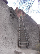. by way of ladders and narrow trails carved out of the tuff walls of the .
