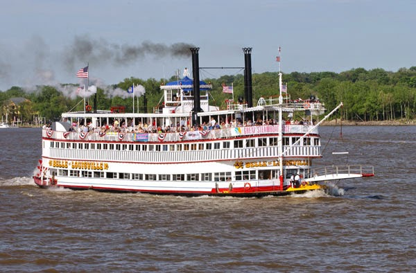 belle of louisville steam boat sailing on the river with black smoke coming out of the top and guests standing on the deck and the paddle wheels churning water on the back and an american flag flying off the top